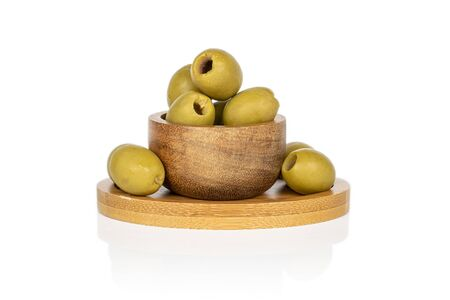 Group of six whole marinated green olive on round bamboo coaster in bamboo bowl isolated on white background