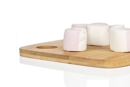 Group of five whole sweet pastel marshmallow on bamboo cutting board isolated on white background