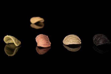 Group of five whole colorful pasta orecchiette in row isolated on black glass Banco de Imagens