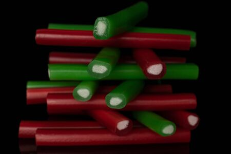 Lot of whole sweet stick candy tower isolated on black glass