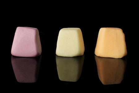 Group of three whole soft pastel candy isolated on black glass