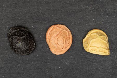 Group of three whole colorful pasta orecchiette in row flatlay on grey stone Banco de Imagens