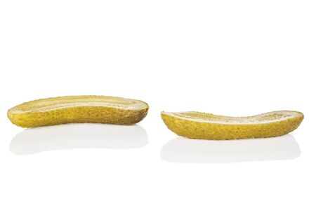 Group of two halves of sour green pickle isolated on white background