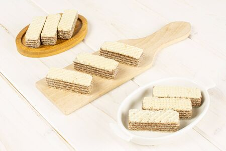 Group of nine whole crispy beige hazelnut wafer cookie in white oval ceramic bowl on bamboo coaster on small wooden cutting board on white wood