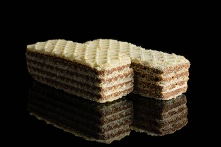 Group of two whole crispy beige hazelnut wafer cookie isolated on black glass 写真素材