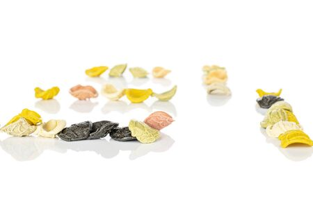Lot of whole arranged colorful pasta orecchiette isolated on white background