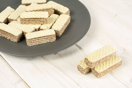 Lot of whole crispy beige hazelnut wafer cookie on gray ceramic plate on white wood