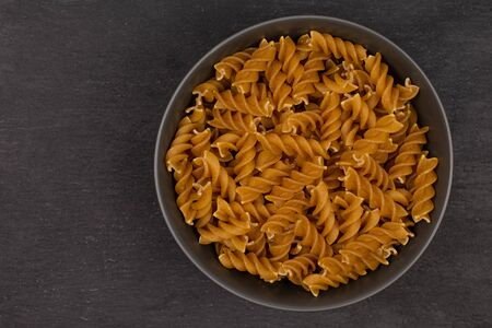 Lot of whole dry brown wholegrain fusilli in gray ceramic bowl flatlay on grey stone