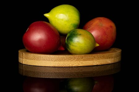 Group of five whole fresh tomato de barao on round bamboo coaster isolated on black glass Stock Photo