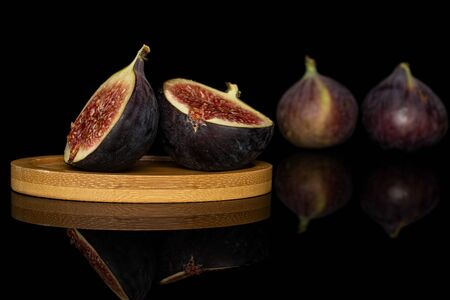 Group of two whole two halves of sweet purple fig on round bamboo coaster isolated on black glass