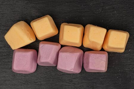 Lot of whole arranged soft pastel candy flatlay on grey stone