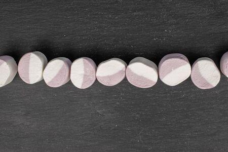 Group of nine whole sweet pastel marshmallow flatlay on grey stone 스톡 콘텐츠