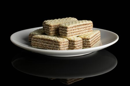 Lot of whole crispy beige hazelnut wafer cookie on white ceramic plate isolated on black glass 写真素材