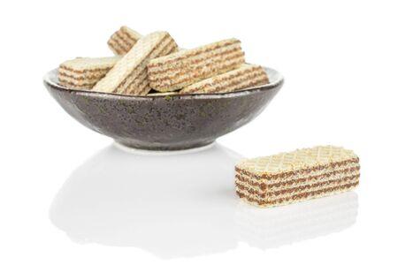 Lot of whole crispy beige hazelnut wafer cookie in dark ceramic bowl isolated on white background