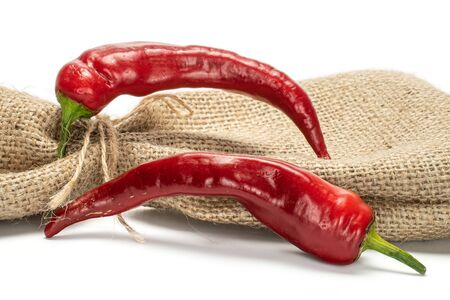 Group of two whole dark red fresh hot pepper with jute bag isolated on white background Stock Photo