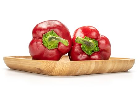 Group of two whole sweet red bell pepper on wooden square plate isolated on white background