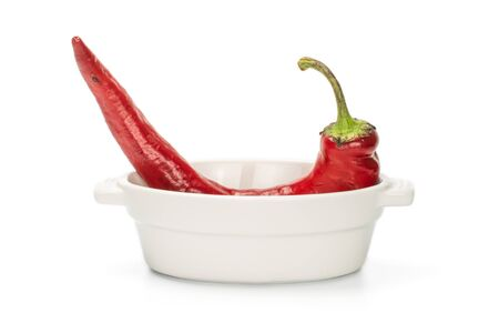 One whole red fresh hot pepper in ceramic stewpan isolated on white background