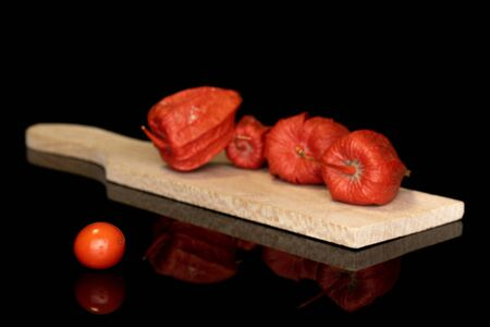 Group of five whole fresh orange physalis on wooden cutting board isolated on black glass