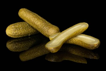 Group of two whole two halves of sour green pickle isolated on black glass