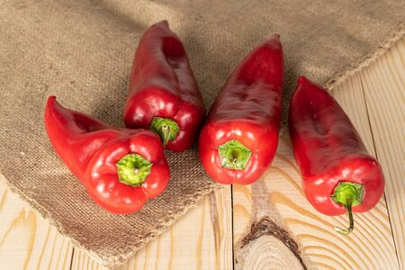 Group of four whole sweet red bell pepper on jute cloth on natural wood Stock Photo