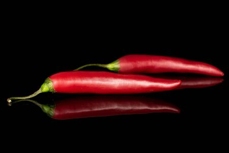 Group of two whole hot red chili cayenne isolated on black glass