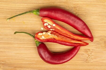 Group of three whole hot red chili cayenne one opened flatlay on light wood