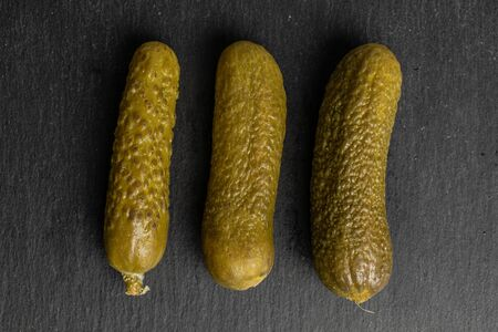 Group of three whole sour green pickle flatlay on grey stone Stock Photo