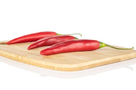 Group of three whole hot red chili cayenne on bamboo cutting board isolated on white background