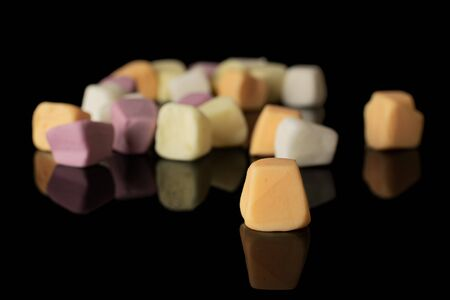 Lot of whole disordered soft pastel candy isolated on black glass