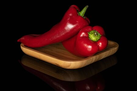 Group of two whole sweet red bell pepper on wooden square plate isolated on black glass
