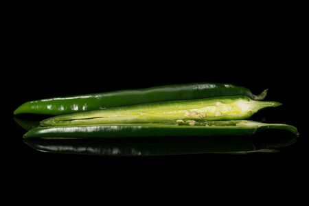 Group of one whole two halves of fresh hot pepper isolated on black glass Stock Photo