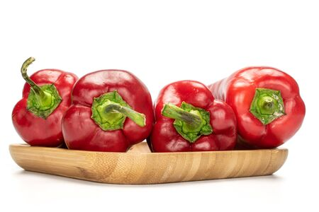 Group of four whole sweet red bell pepper on wooden square plate isolated on white background Stock Photo