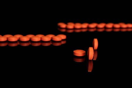 Lot of whole orange tablet pharmacy front focus isolated on black glass Stok Fotoğraf