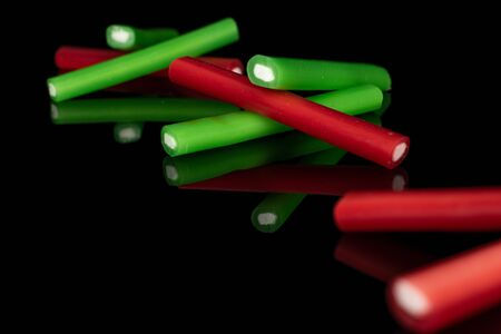 Group of eight whole sweet stick candy isolated on black glass