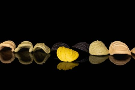 Group of eight whole colorful pasta orecchiette isolated on black glass