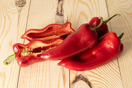 Group of three whole two halves of sweet red bell pepper on natural wood