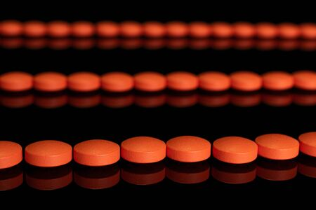 Lot of whole orange tablet pharmacy in row isolated on black glass Stok Fotoğraf