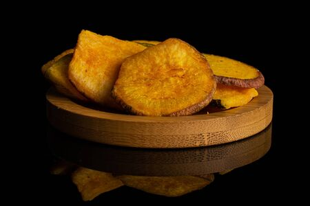 Lot of whole dry vegetable chip of gourd on bamboo coaster isolated on black glass