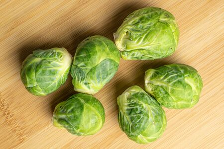 Group of six whole fresh green brussels sprout flatlay on light wood