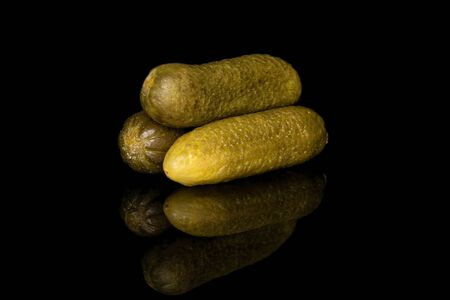 Group of three whole sour green pickle isolated on black glass
