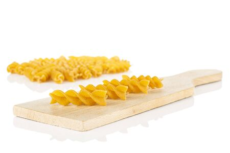 Lot of whole dry brown wholegrain fusilli on small wooden cutting board isolated on white background
