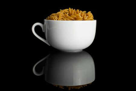 Lot of whole dry brown wholegrain fusilli in white ceramic cup isolated on black glass 스톡 콘텐츠