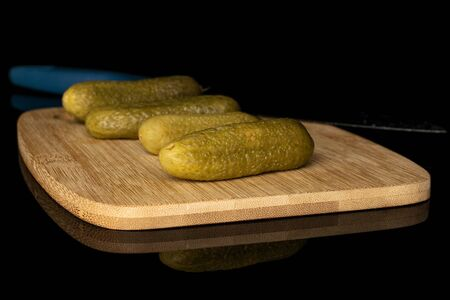 Group of four whole arranged sour green pickle on bamboo cutting board with steel knife isolated on black glass