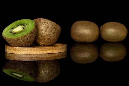 Group of two whole two halves of exotic brown kiwi on round bamboo coaster isolated on black glass Reklamní fotografie
