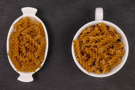 Lot of whole dry brown wholegrain fusilli in white oval ceramic bowl in white ceramic cup flatlay on grey stone