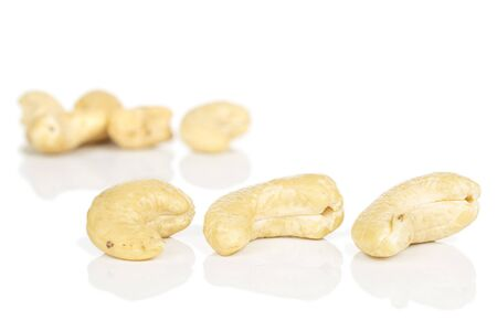 Lot of whole brown nut cashew three in focus isolated on white background
