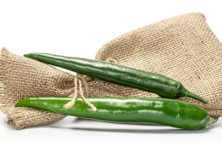 Group of two whole green fresh hot pepper with jute bag isolated on white background Stock Photo