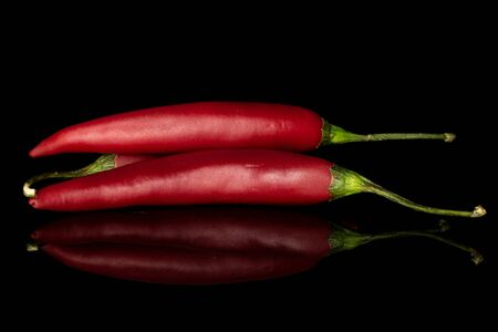 Group of three whole hot red chili cayenne isolated on black glass Stock Photo