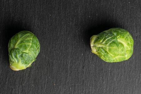 Group of two whole fresh green brussels sprout flatlay on grey stone 版權商用圖片