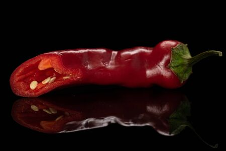 One half of fresh hot pepper isolated on black glass Stock Photo